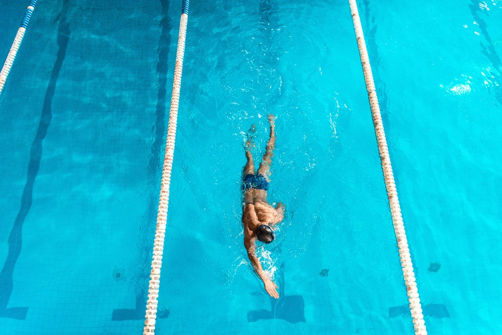 overhead view of swimmer in competition swimming pool with lines