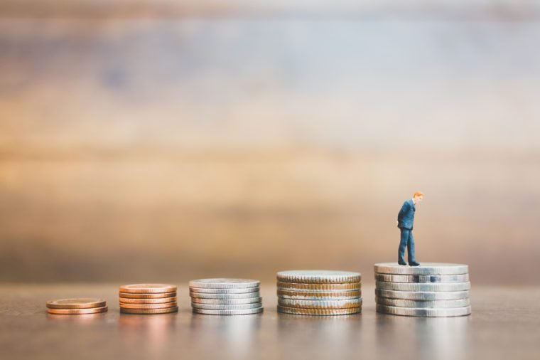 Miniature people businessman standing on money with wooden background