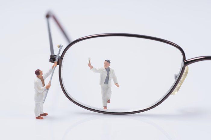 miniature people worker cleaning eyes glasses