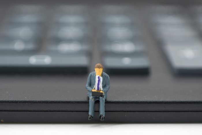Miniature people: businessman sitting on calculator. Financial, and business concept