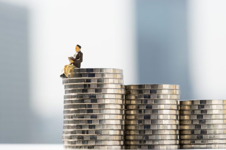 Commercial Money and banking financial concepts. Miniature people: Business man sitting / reading book on pile of coin with blurred colorful background.