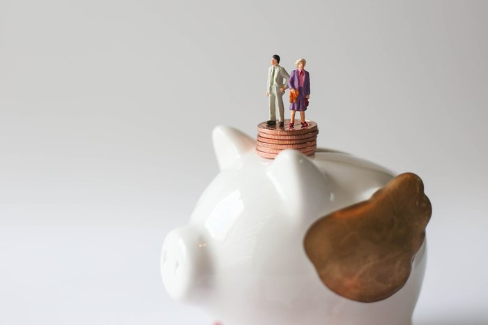 Miniature people: Man and woman standing on stack of coins with piggy bank using as background family day, business concept.