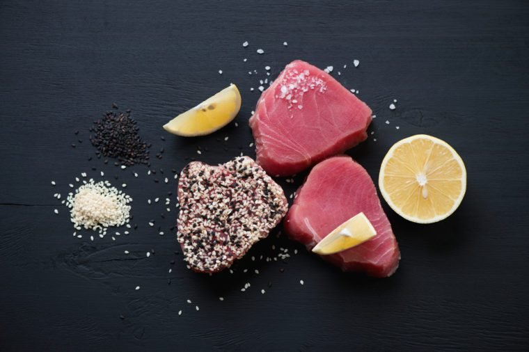 Raw tuna steaks with sesame, black wooden surface, flat-lay view
