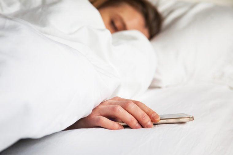 woman sleeping in bed being woken by mobile phone