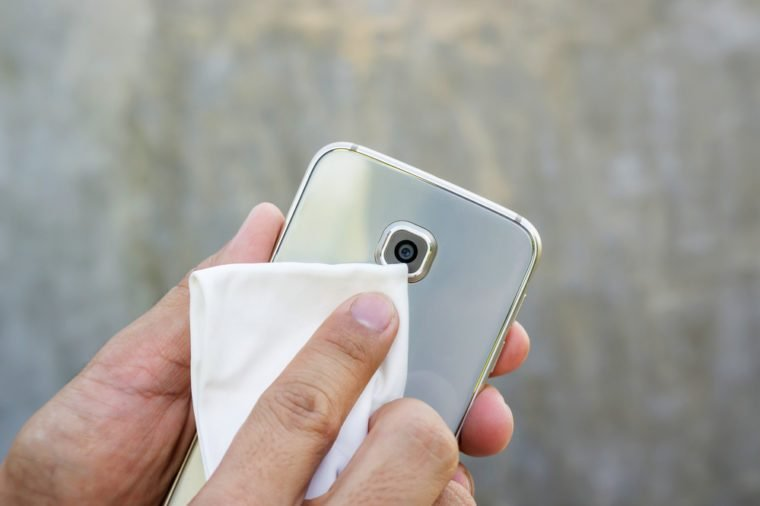 Man cleaning his smartphone with a microfiber cloth.