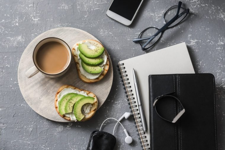 Coffee break during working hours. Flat lay business workplace with notebook, tablet, phone, glasses. Coffee and sandwich with cream cheese and avocado on a gray background, top view