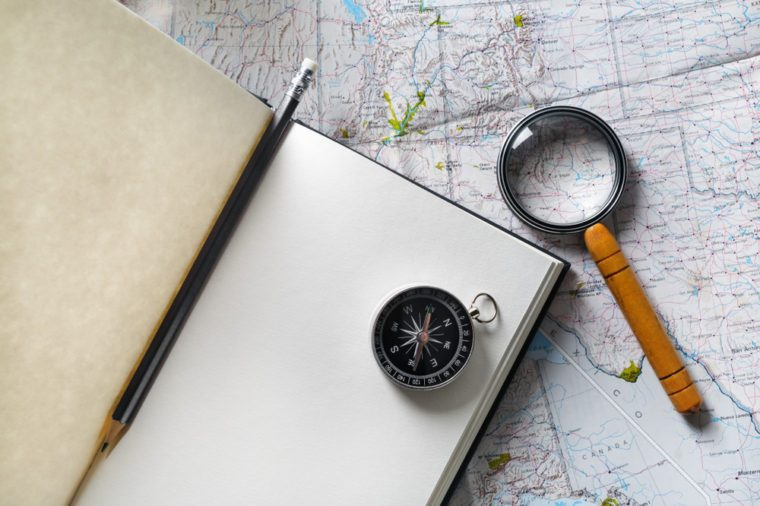 Travel plan background. Ready for the trip. Map, blank notebook, magnifier, compass and pencil. Flat lay