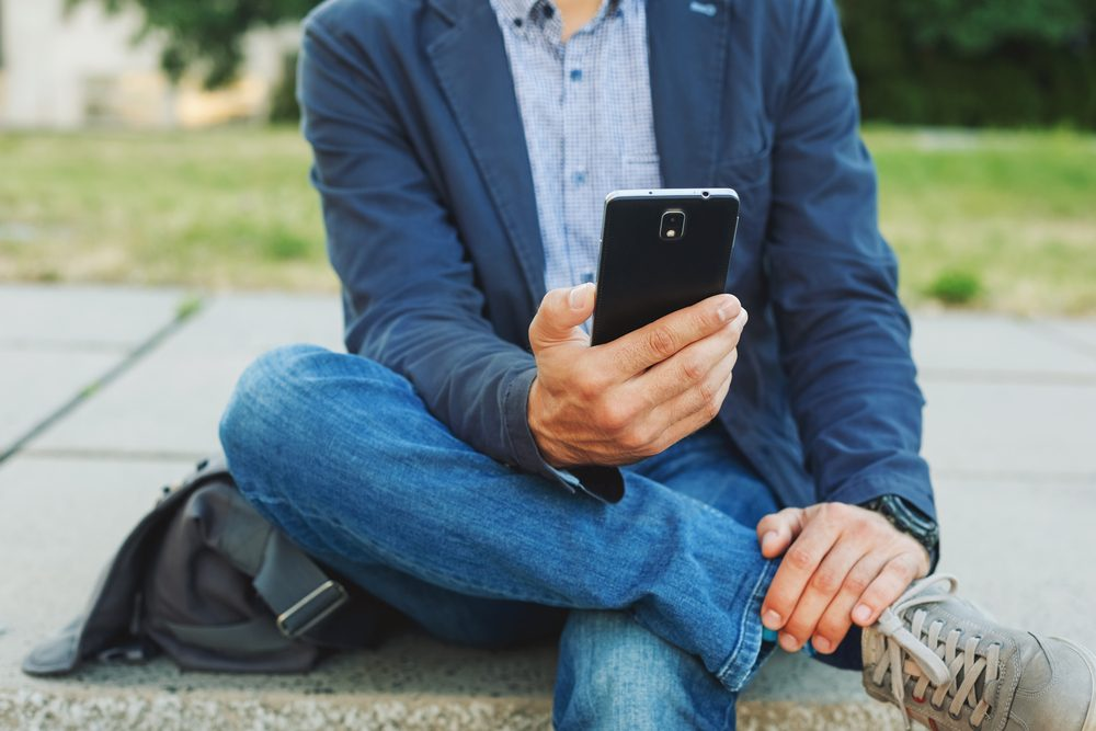 Young casual man using smart phone sitting outdoor