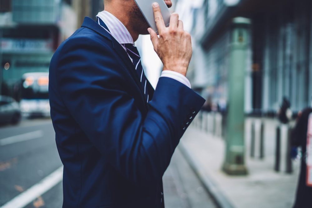 Cropped image of businessman holding phone in hands while having phone conversation during walk to office, close up male person in suit calling mobile in roaming using tariffs, people communicating