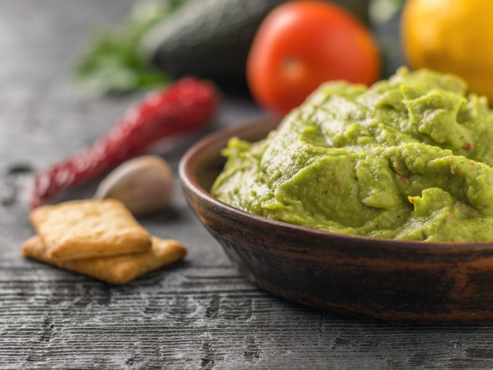 Clay bowl with fresh guacamole, tomatoes, lemon, chips and garlic on wooden table. Diet vegetarian Mexican food avocado.