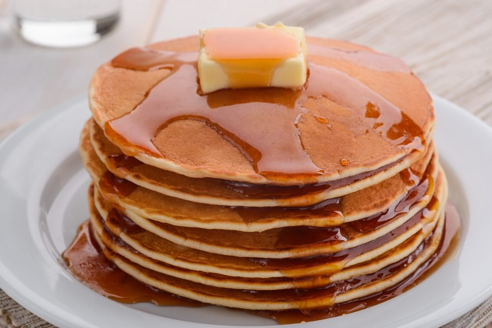 Sunny golden-brown pancakes showered with syrup. Butter slowly melts on top of the stack. A dish with tasty breakfast in the foreground.