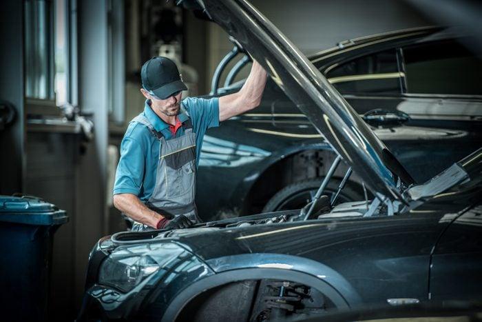 Car Mechanic and His Job. Caucasian Auto Service Worker in Front of Broken Vehicle.