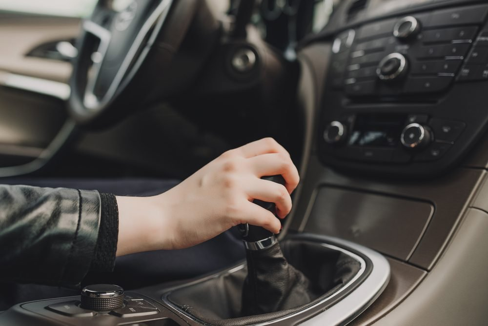 Close up of hand of female driver shifting gear stick before driving car