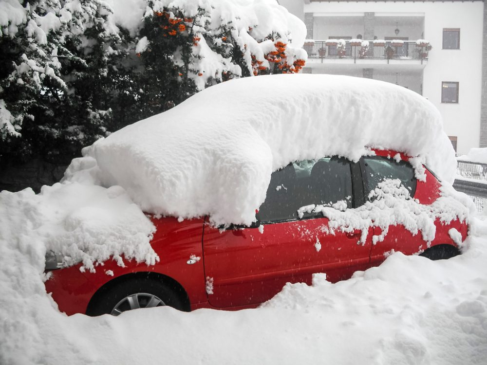 A red car covered by snow at Valpelline Village, Aosta Valley Province, Italy