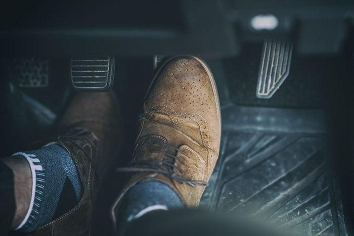 Man foot press the break pedal of a car.
