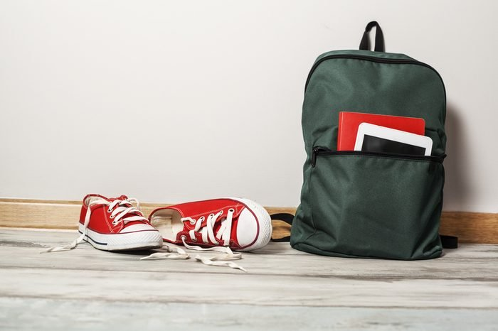 Red sneakers with school bag on wooden background