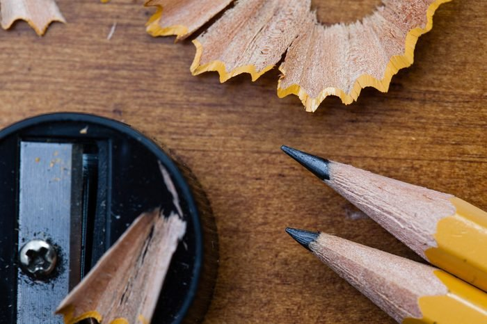 A macro image of two sharpened pencils, a sharpener, and their shavings