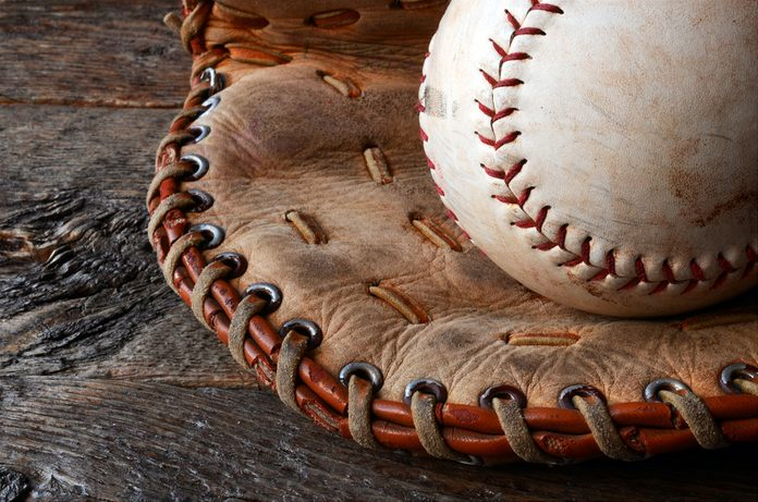 A low angle image of an old used baseball and leather baseball glove.