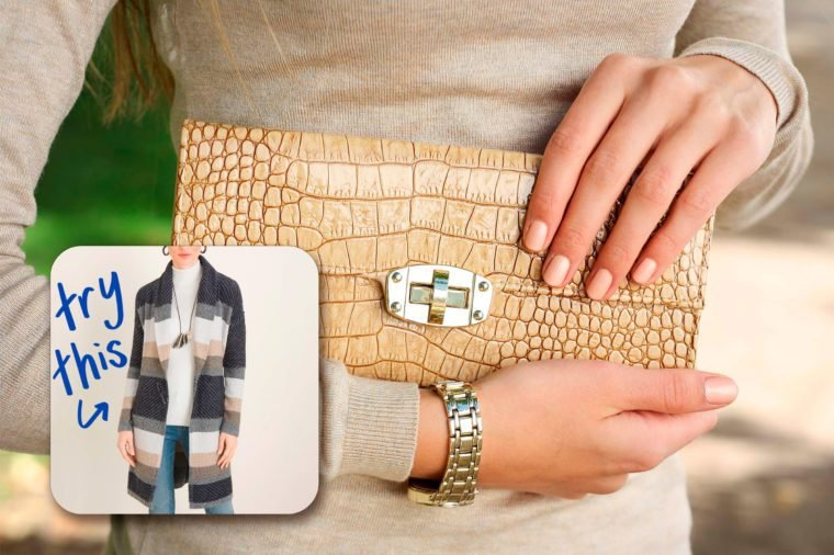 womans hands holding clutch purse.