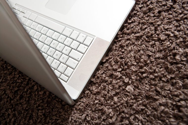 Over head view of a silver open laptop computer lying on a woolly brown blanket in a hotel room. Technology still life object with no people, interior.