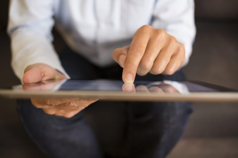Man using a Tablet Pc on sofa, indoor