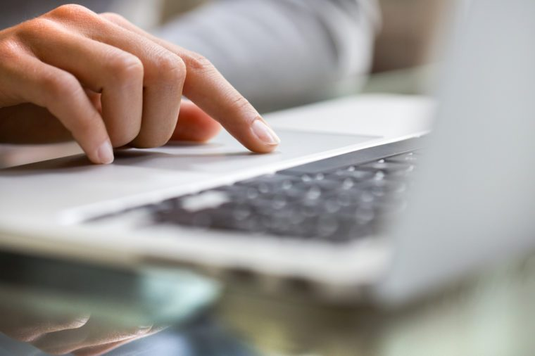 Woman using laptop indoor.close-up hand