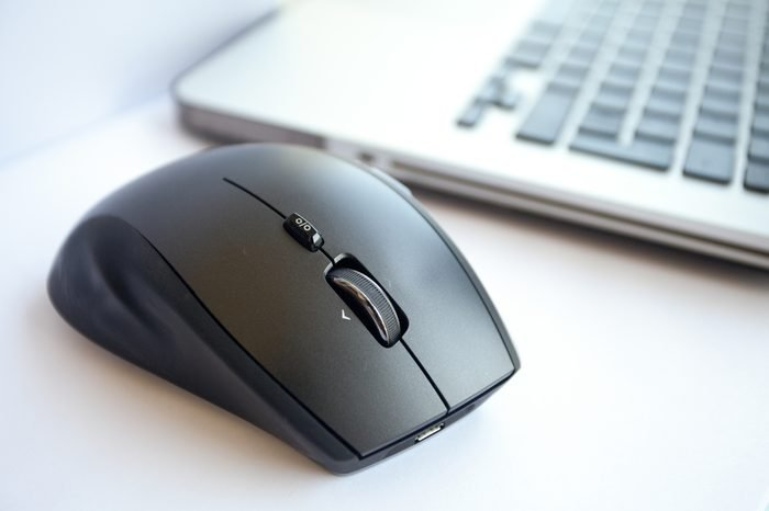 Wireless mouse is located near the laptop. White background, close up