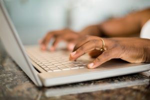 Close up of masculine hands typing on laptop keyboard