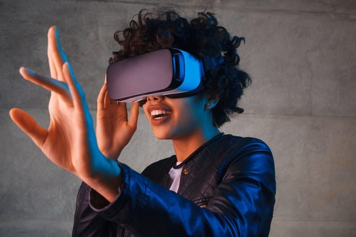 Amazed young woman touching the air during the VR experience. Horizontal studio shot.