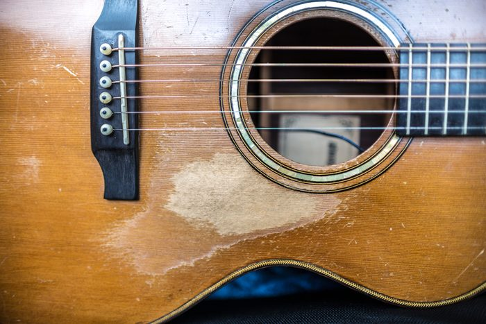 Handmade Cedar Acoustic Guitar with worn relic in dark toned color and selective soft focus