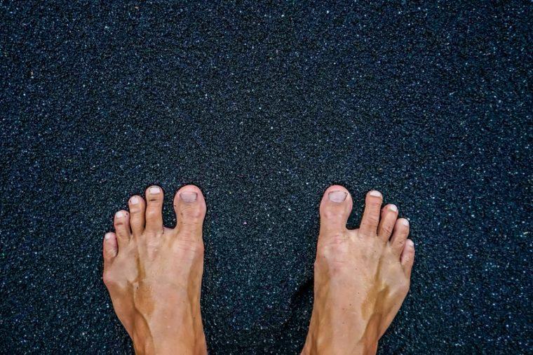 feet on black sand beach