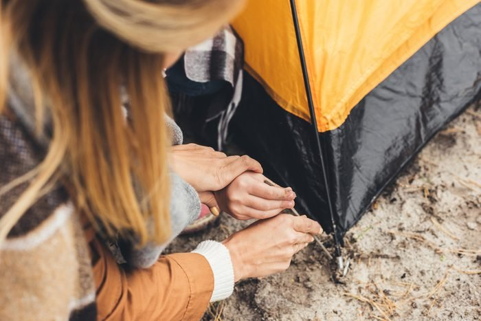 cropped shot of mother and kid installing camping tent