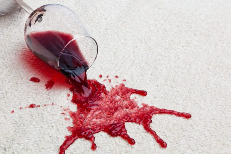 A toppled glass of red wine with a dirty carpet.