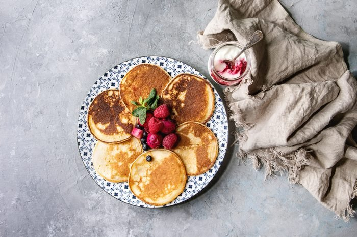 Homemade pancakes served on decorate plate with berries, mint, glass jar of yogurt and cloth over grey texture background. Top view, space.