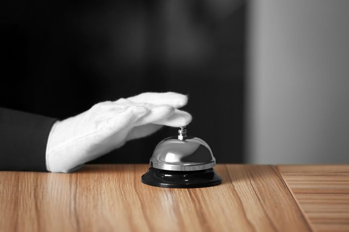 Man ringing service bell on wooden table