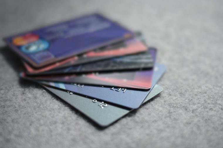 Colorful stack of credit cards and shopping gift cards on gray carpet back ground. Extremely shallow dof.
