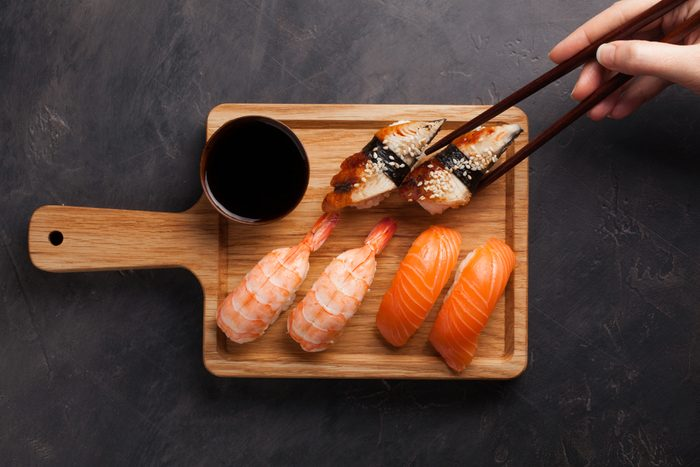 A set of sushi with salmon, shrimp and eel and wooden chopsticks on a wooden Board. Delicious Japanese food on a dark stone background. female hand takes the chopsticks in the sushi. Top view.
