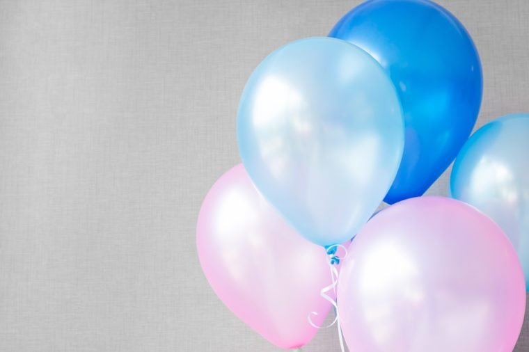 blue and pink balloons on gray wall