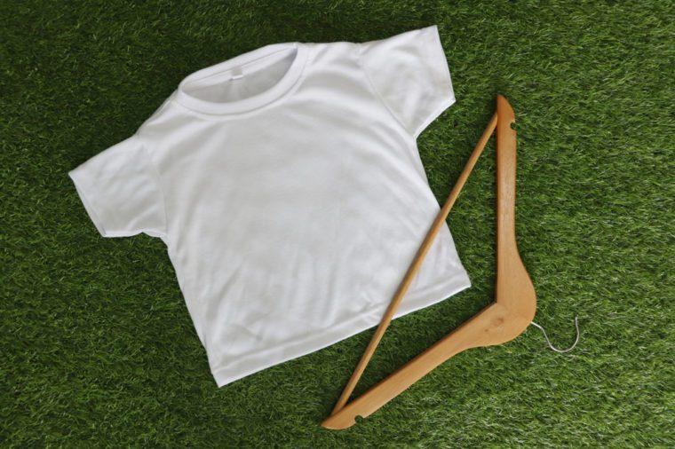 kid white blank t-shirt on green background, cloth hanger on grass.