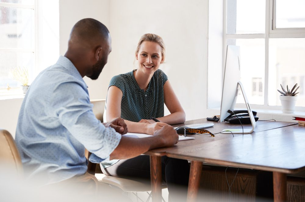 Man and woman sitting at a desk talking in an office smiling