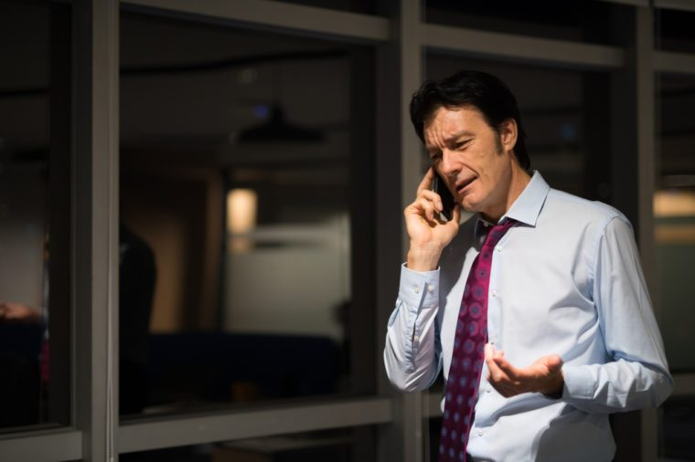 Mature Businessman In Office At Night Talking On Mobile Phone