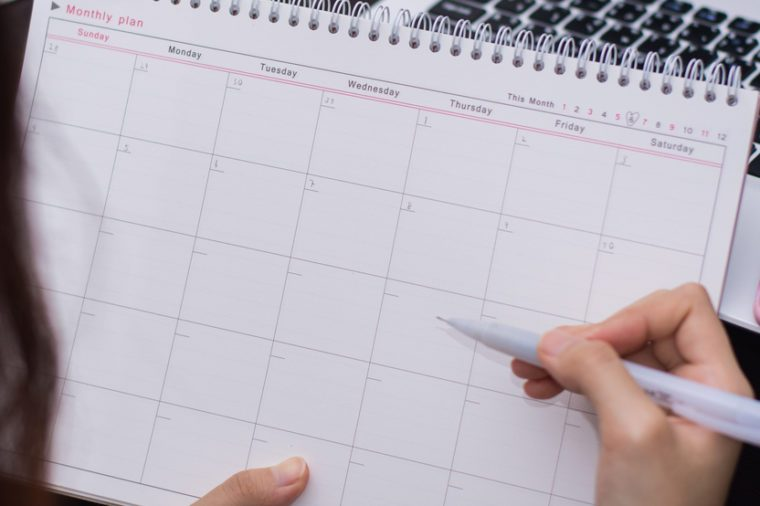hand of women planning on calender at her office