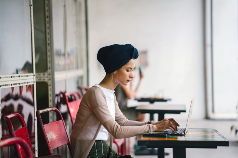 A young Muslim woman wearing a turban (hijab) is working on her laptop computer at a wooden table in the day. She is elegant, beautiful and professional.