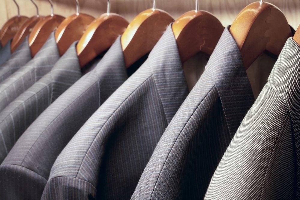Row of men's suit jackets hanging in closet