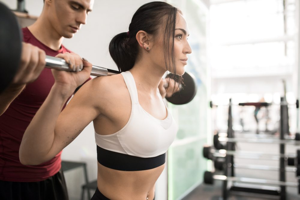 Waist up portrait of fitness coach helping beautiful young woman training with barbell in modern gym, copy space