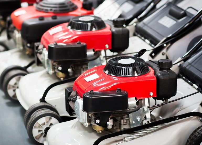 Showcase of the new powerful red gasoline lawn mower in the store (shop). Indoor shoot with nobody.