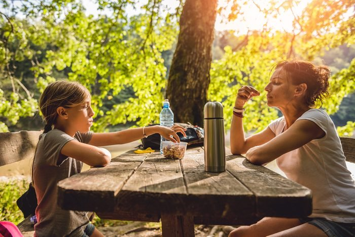 Mother and daughter eating healthy snack at a picnic table in the forest