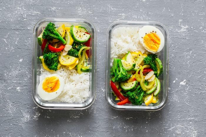 Vegetarian lunch box - stewed vegetables, rice and boiled egg on a gray background, top view. Health food concept