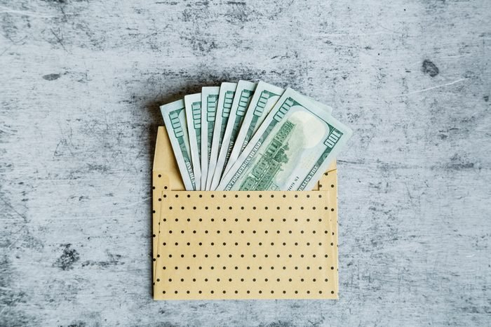 Desktop flatlay: the envelope with one hundred dollars bills lying on gray marble background