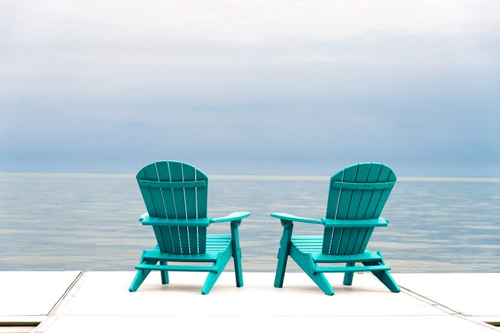 Adirondack Chairs at the end of a pier overlooking a large blue lake with a blue sky